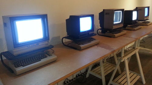 Five Commodore 64s running one-line programs